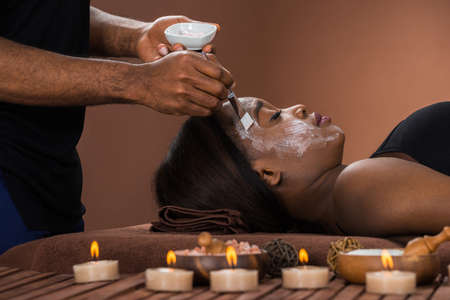 Young African Woman Getting Facial Mask At Spa Фото со стока