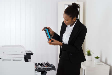 photocopier: Young African Businesswoman Fixing Cartridge Near Photocopy Machine In Office