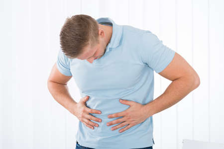 digestive disease: Young Man Suffering From Stomach Ache Standing At Home