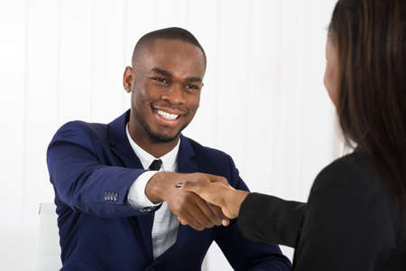 Successful African American Businessman Handshaking With Client In Office Stock Photo