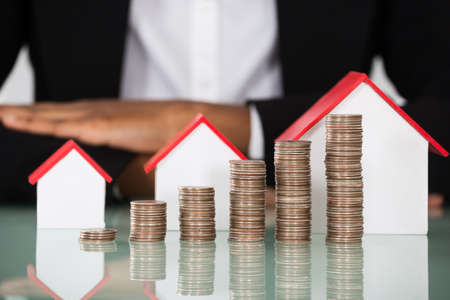 Close-up Of Businesswoman With Different Size Of House Model And Stacked Coins On Desk Stock Photo
