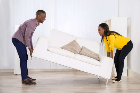 by placing: Young Happy African Couple Placing Sofa In Living Room Stock Photo