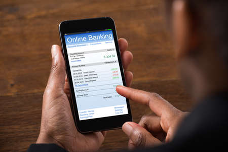 Close-up Van Jonge Onderneemster Met Online Bankieren Op Mobiele Telefoon In Kantoor Stockfoto - 56064819