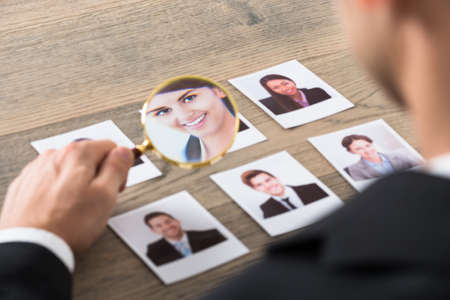 candidates: Close-up Of A Businessman Viewing Candidates Through Magnifying Glass At Desk In Office