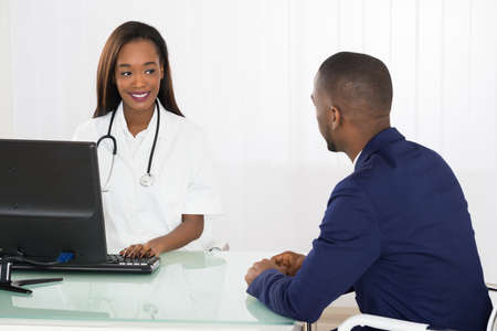 black professional: African American Doctor And Patient Discussing On Computer At Diagnostic Center