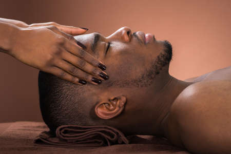 black male: Young African Man Receiving Forehead Massage In Spa Stock Photo