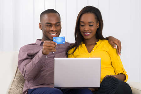 house shopping: Happy Young African Couple Shopping Online With Credit Card At Home