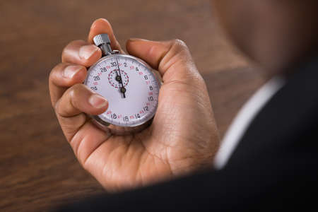 timekeeping: Close-up Of A Businessperson Hand Holding Stop Watch Stock Photo