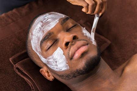Terapeuta aplicación de la mascarilla Para africano del hombre joven en balneario