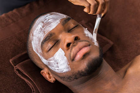 peel: Therapist Applying Face Mask To Young African Man In Spa