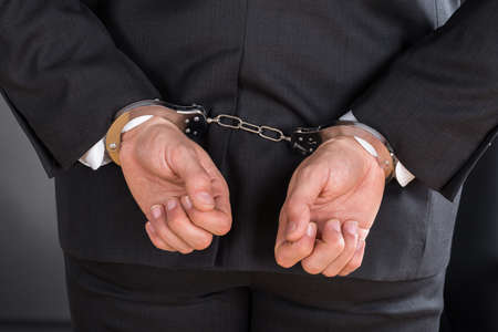 criminal: Close-up Of Businessman In Handcuffs Arrested For Crime Stock Photo