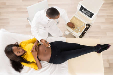 transducer: Gynecologist Moving Ultrasound Transducer On Pregnant Womans Belly While Looking At Screen In Hospital Stock Photo