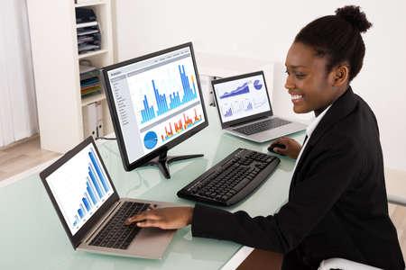 Jonge Afrikaanse Zakenvrouw analyseren van grafiek op het computerscherm