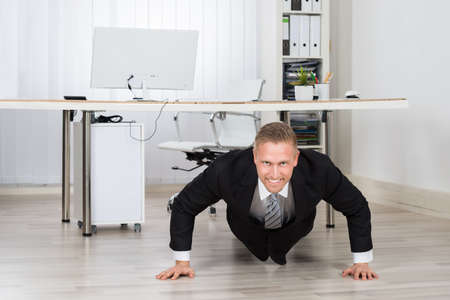 Young Businessman Doing Pushup At Work In Office