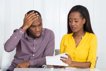 Sad Jeune couple africaine Regardant le projet de loi Banque d'images