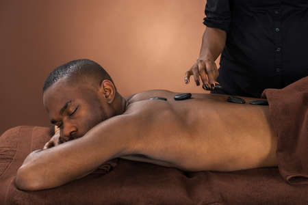 massager: African Man Relaxing In A Spa Getting Hot Stone Therapy Stock Photo