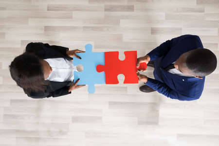 business puzzle: Business Man And Woman Holding Puzzle Pieces And Showing Their Teamwork