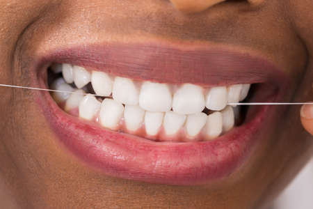 flossing: Close-up Of Young African Woman Flossing Teeth