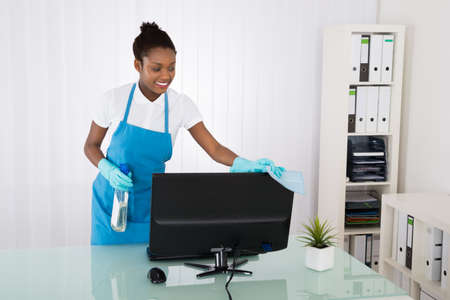 janitor: Happy Female Janitor Cleaning Computer With Rag In Office Stock Photo