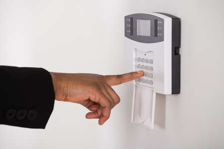 entry numbers: Close-up Of Young Businesswoman Hand Entering Code In Security System Stock Photo