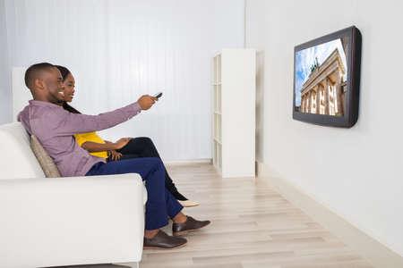 pareja viendo television: Feliz pareja sentado en el sofá Televisión de observación