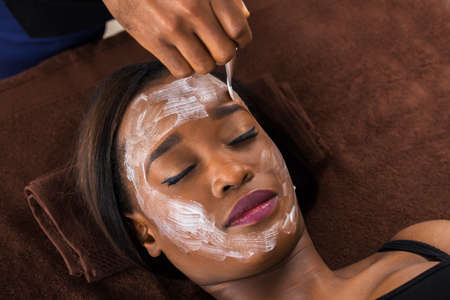 chemical peels: Close-up Of Young African Woman Applying Facial Mask In Spa