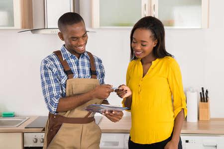 Junge Glückliche Frau Und Serviceman Stehen in der Küche mit Zwischenablage Standard-Bild
