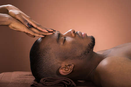 black lady: Young African Man Receiving Forehead Massage In Spa Stock Photo
