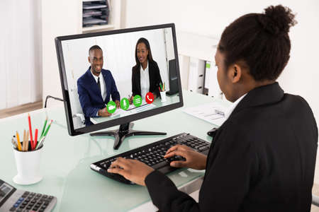 videoconferencing: Young African Businesswoman Videoconferencing With Colleagues On Computer