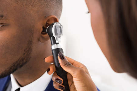 otoscope: Close-up Of Doctor Examining Male Patients Ears