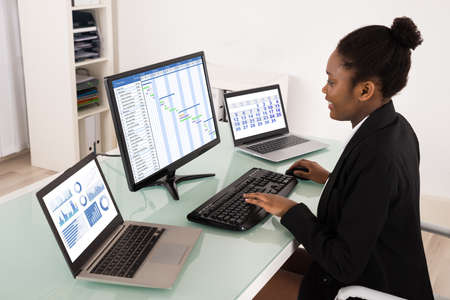 gantt: Young African Businesswoman Working On Gantt Chart In Office Stock Photo