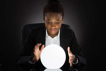 magic ball: Young African Businesswoman Predicting Future With Crystal Ball On Desk Over Black Background