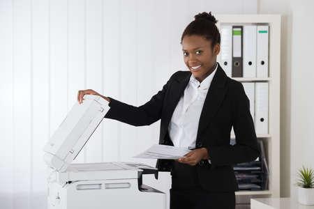 Glimlachende Jonge Afrikaanse Zakenvrouw Het plaatsen van papier op kopieermachine In Office