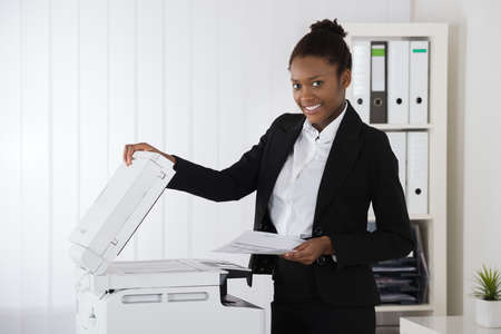 Smiling Young African Businesswoman Placing Paper On Photocopy Machine In Office