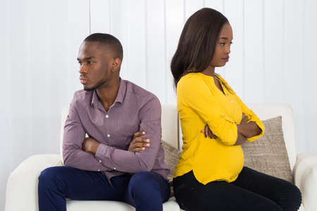 Young Unhappy African Couple Sitting Back To Back On Sofa At Home
