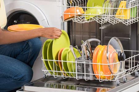 utencilios de cocina: Primer plano de la mano de la mujer que arregla platos en lavavajillas en casa