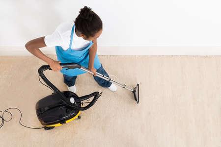 personal de limpieza: Vista de ángulo alto de mujer joven limpieza de piso de limpieza con aspiradora