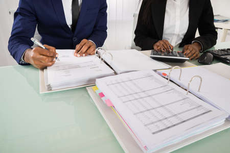 account executive: Close-up Of Two Businesspeople Calculating Invoice With Calculator At Desk Stock Photo