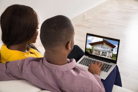 Young Couple Looking At House On Laptops Screen Stock Photo