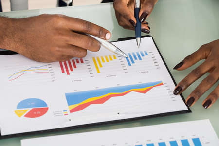 analyzed: Close-up Of Businesspeople Analyzed By Graphs And Charts At Workplace Stock Photo