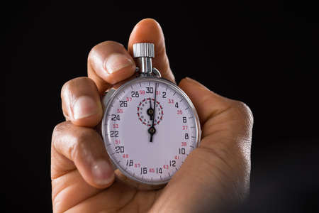 timekeeping: Close-up Of A Person Holding Stop Watch Over Black Background Stock Photo