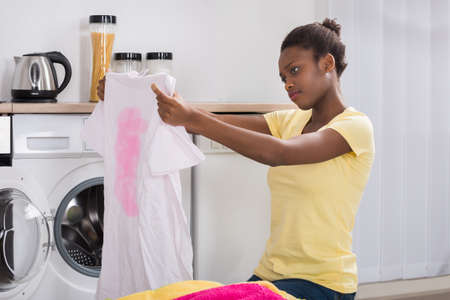 wash cloth: Young African Woman Looking At Stained Cloth In Kitchen