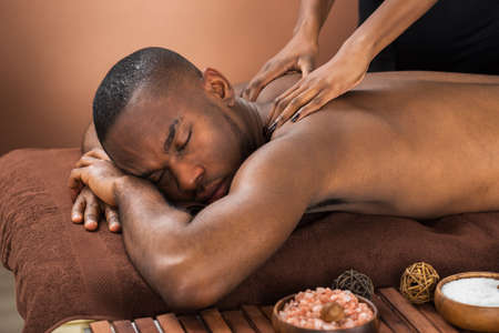 Close-up Of Happy African Man Receiving Massage Treatment