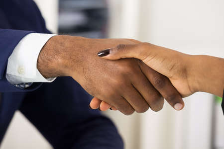 black hands: Close-up Of Two African People Shaking Hands Stock Photo