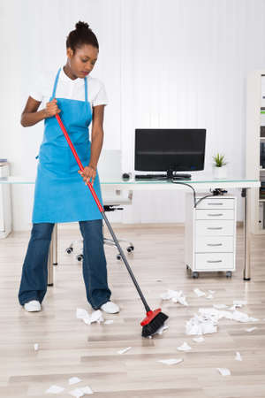 janitor: Young Female Janitor Sweeping Torn Paper Pieces On Hardwood Floor