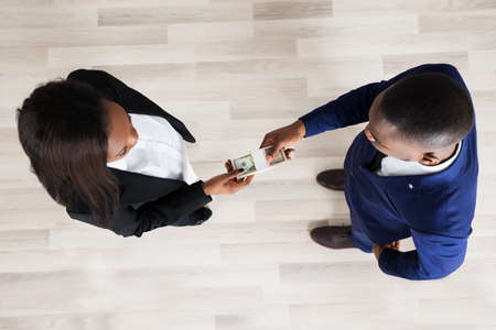executive woman: Elevated View Of Business Man And Woman Exchanging Money