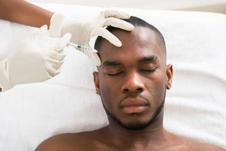 medical treatment: Close-up Of Person Hand Injecting Syringe On Young African Man Face Stock Photo
