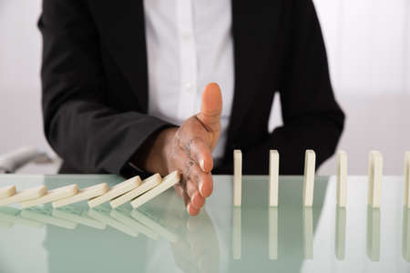 dominoes: Close-up Of Businesswoman Hand Stopping Dominoes From Falling On Office Desk Stock Photo