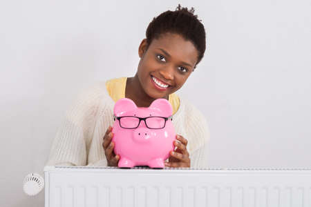 american money: Young African Woman Leaning On Radiator With Pink Piggybank At Home
