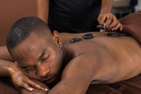 stone therapy: African Man Relaxing In A Spa Getting Hot Stone Therapy Stock Photo